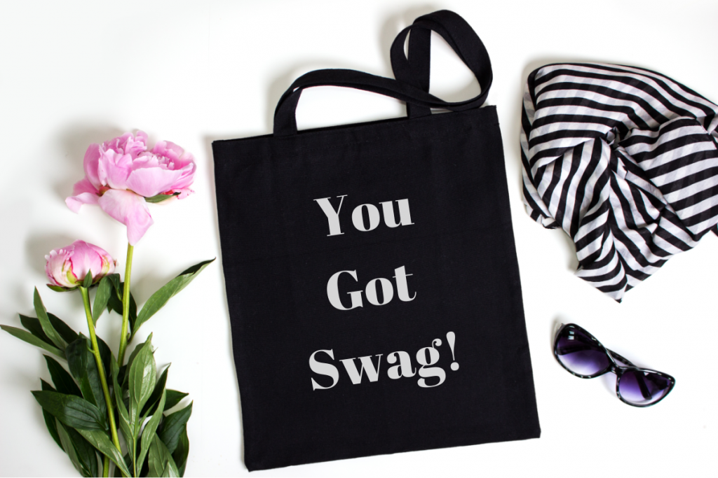 """Company Swag - Image from Canva of a black canvas tote that says """"you got swag!' on it, next to a scarf and sunglasses and a stem of peonies"""